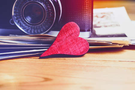 wooden heart as love symbol near photo camera and photo cards