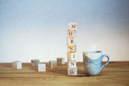 Cup of fresh coffee with Morning word written in wooden blocks