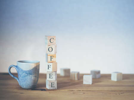 Cup of fresh coffee with word written in wooden blocks