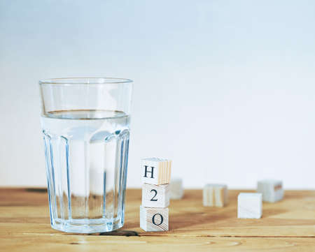 Glass of pure water with H2O formula written in wooden blocks