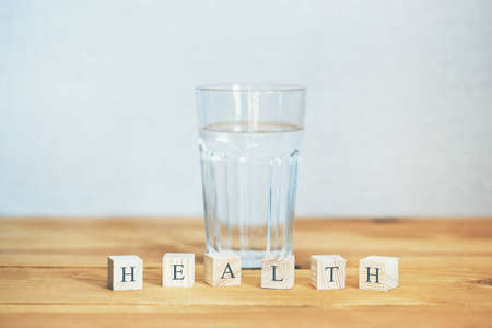 Glass of pure water with health word written in wooden blocks Banco de Imagens