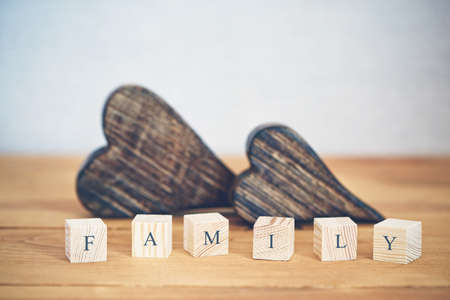 Two wooden hearts with Family word written in blocks Stock Photo