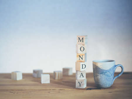 Cup of fresh coffee with Monday word written in wooden blocks Stock Photo