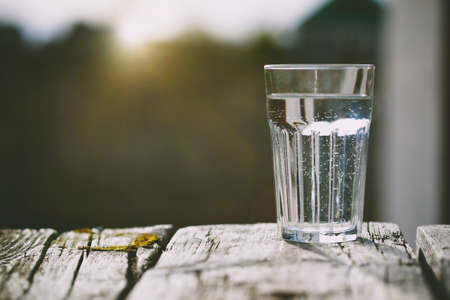 Glass of pure water on natural sunrise background with copy space Stock Photo
