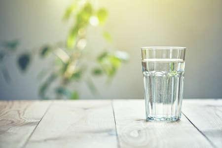 Glas zuiver water op zonlichtachtergrond met natuurlijke installatie Stockfoto