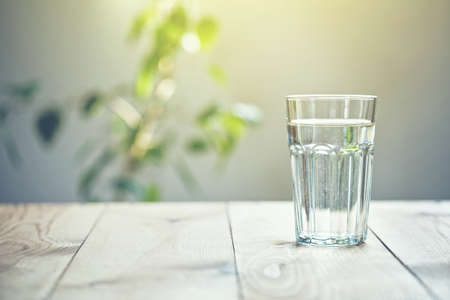 Glass of pure water on sunlight background with natural plant Imagens
