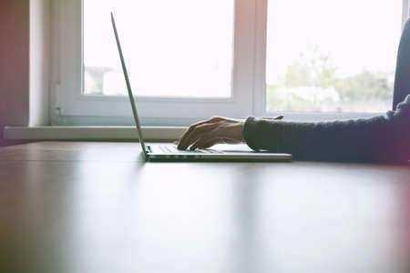 girls hands working with laptop near window