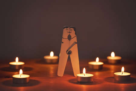 Happy couple in love. Wooden pin with painted funny faces of lovers in night candle light