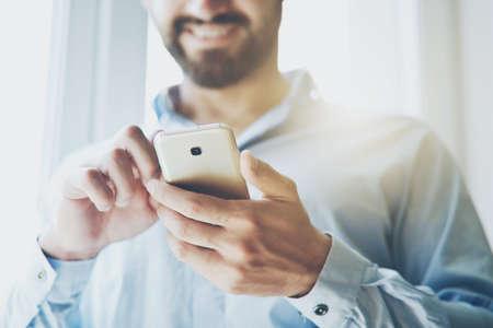 Smiling businessman using smart phone in sunlight Stock Photo