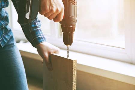 mans hands drilling wooden plank