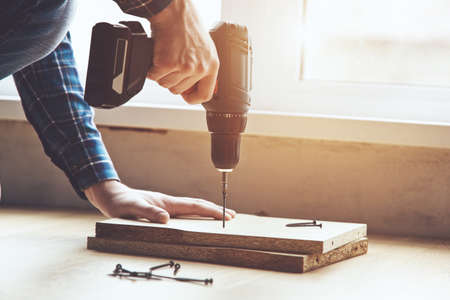 mans hands working with electric screwdriver and wooden plank
