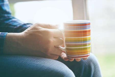 man sitting near window with cup of morning coffee or tea