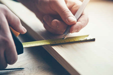 mans hands working with wood measuring tape and marking with pencil