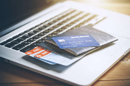 Air tickets, passports and credit card near laptop. Online ticket booking concept