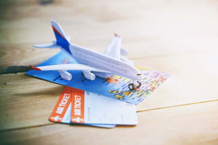 Plane model with world map and tickets as airplane traveling and tickets booking concept