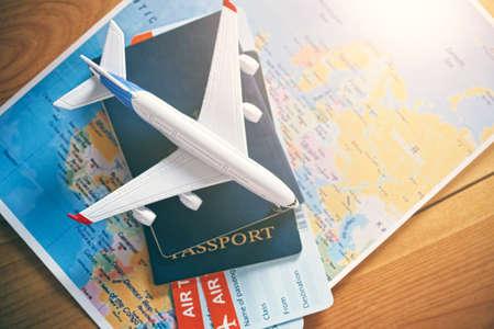 Modello di aereo con mappa del mondo, passaporti e biglietti come viaggio in aereo e concetto di prenotazione di biglietti