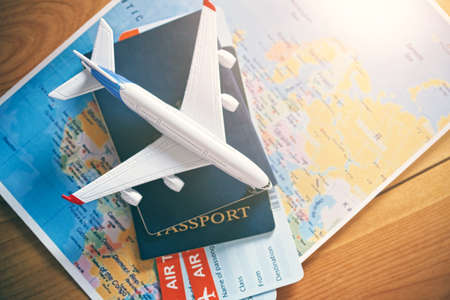 Plane model with world map, passports and tickets as airplane traveling and tickets booking concept
