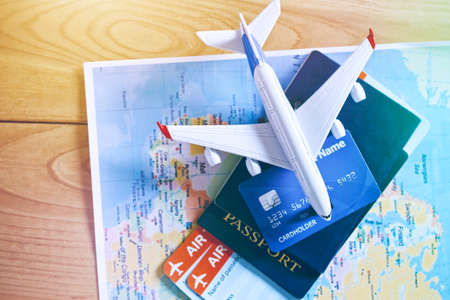 Air tickets, passports and credit card on world map. Online ticket booking and holiday planning concept Stock Photo