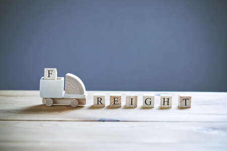 Wooden model of truck loading freight cubes with text. Shipping and delivery concept