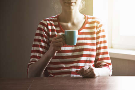 girls hands with cup of coffee or tea in morning light Stock Photo