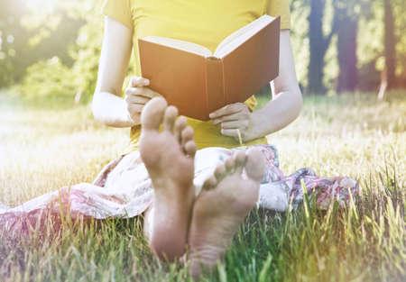 girl reading book in warm summer grass