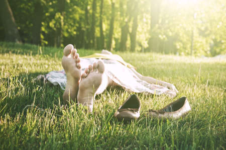 girls legs lying in grass barefoot without shoes Stock Photo