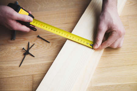 mans hands working with wood measuring tape