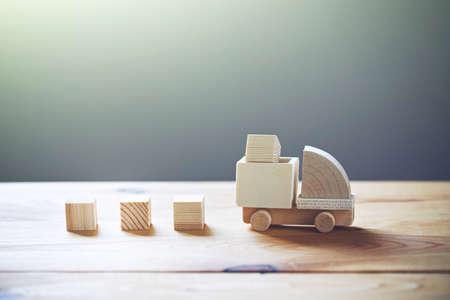 Drewniany model ciężarówki ładującej towar. Koncepcja wysyłki i dostawy