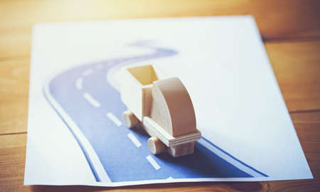 Wooden model of truck moving on abstract road. Shipping and delivery concept Stock Photo