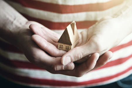 hands holding wooden model of house as symbol