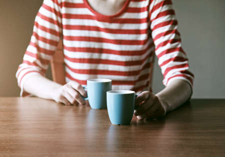 girl with two cups of coffee or tea in morning light offering one for us Stock Photo