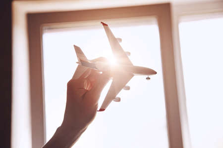 hand with airplane model in sunlight Stock Photo