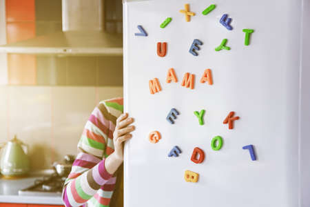 Woman looking in open fridge with Mama letters on door. Cooking for family and children concept 版權商用圖片 - 106200795