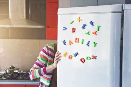 Woman looking in open fridge with Family letters on door. Cooking for children and husband concept