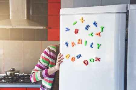 Kobieta szuka w otwartej lodówce z listami rodziny na drzwiach. Gotowanie dla koncepcji dzieci i męża
