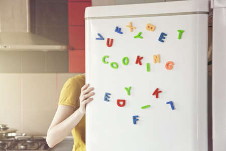 Woman looking in open fridge with Cooking  letters on door. Cooking for family and children concept