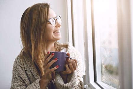 pretty girl drinking coffee or tea in morning sunlight near window
