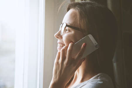 pretty woman talking on phone near window at home Stock Photo - 105532016