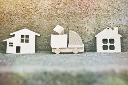 Wooden model of cargo truck delivering box to house. Shipping and transportation concept Stock Photo
