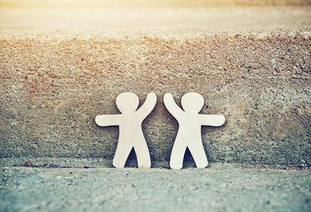 Wooden little men holding hands. Symbol of friendship, love and teamwork