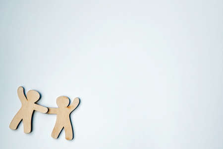 Wooden little men holding hands with blank white space for text or logo. Symbol of friendship, love and teamwork Stock Photo
