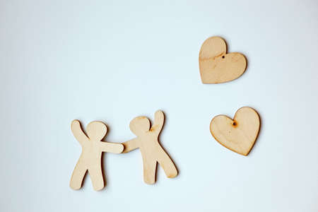 Wooden little men holding hands with wooden hearts. Symbol of love and family