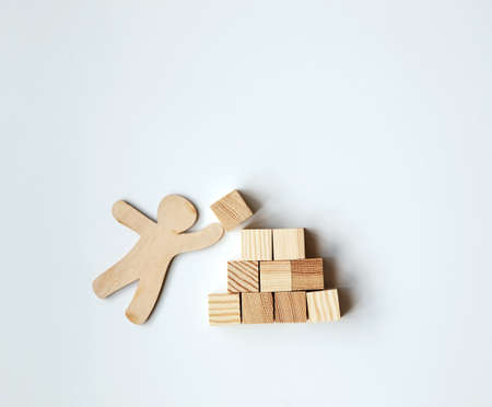 Little wooden man putting block on top of mountain as symbol. Achievement, success, leadership and construction concept