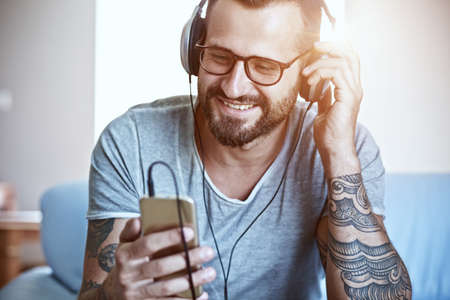 smiling man listening to music with headphones and smart phone Imagens