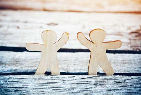 Wooden little men holding hands on natural sunlight background. Symbol of friendship, love and teamwork