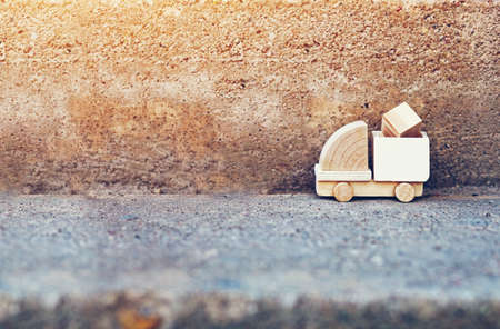 Wooden model of truck loading freight on abstract road. Shipping and delivery concept