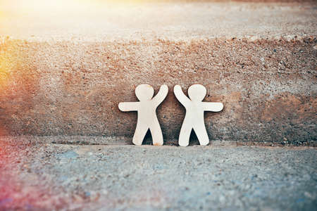 Wooden little men holding hands on natural stone background. Symbol of friendship, love and teamwork Stock Photo