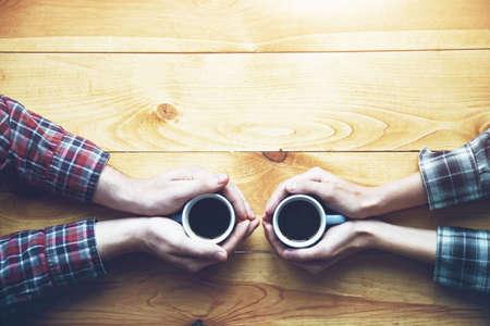 Manos de pareja con dos tazas de café por la mañana en la mesa de madera. Vista desde arriba