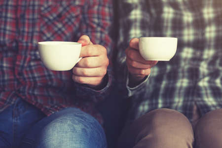 couple with two cups of morning coffee in plaid shirts Stock Photo