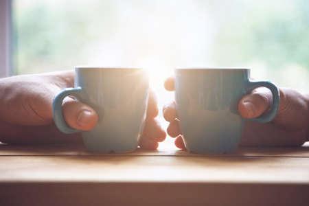 pareja con dos tazas de café por la mañana a la luz del amanecer